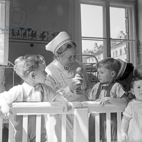 A sister with children of the Red Cross hospital children medical unit at Munich, Germany 1930s (b/w photo)