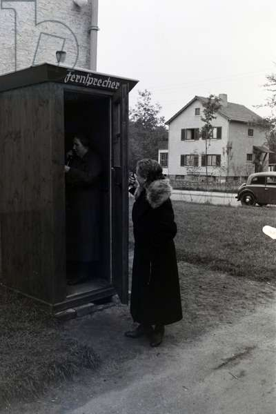 Two women in long coats using the public telephone, phone booth in the zeppelin village near Frankfurt am Main, Germany 1930s (b/w photo)