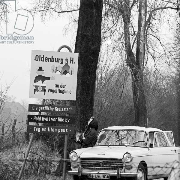A woman with a Peugeot car at the sign of Oldenburg in Holstein, Germany 1960s