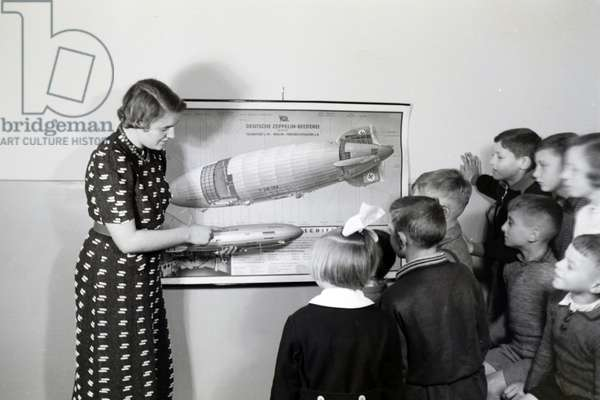 In the school of the zeppelin village near Frankfurt am Main, already the youngest pupils were instructed in the structure of a zeppelin by their teachers, here with the help of an aircraft model, Germany 1930s (b/w photo)
