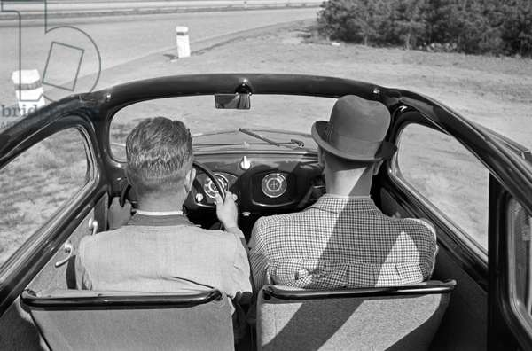 View to the front seats and the car dashboard of the Volkswagen beetle, or KdF car, model with folding top, Germany 1930s (b/w photo)