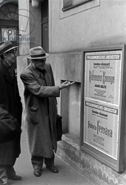Japanese conductor Hidemaro Konoye with a poster of his concert in Germany, 1940s (b/w photo)