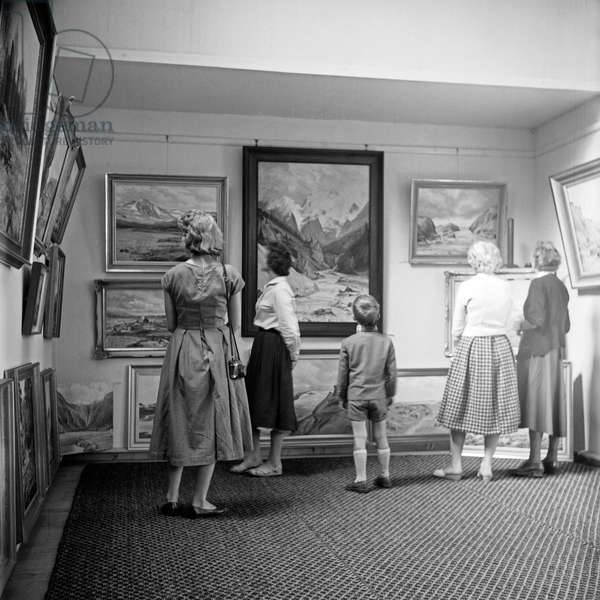 Visitors watching paintings at an exhibition, Germany 1950s