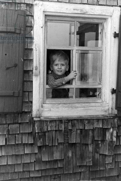 A little boy looking out of the window, Germany 1930s (b/w photo)