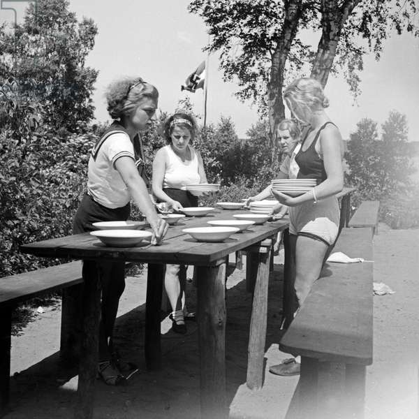 Girls of the BDM nazi youth organization for girls setting the table at leisure camp in Altenhof, Brandenburg, 1930s (b/w photo)