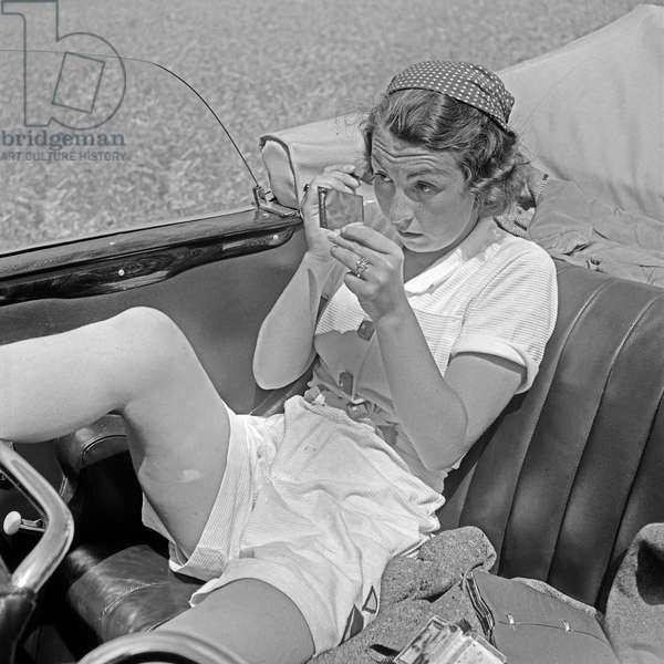 A young woman doing her make up at the backseat of a convertible, Germany 1930s (b/w photo)