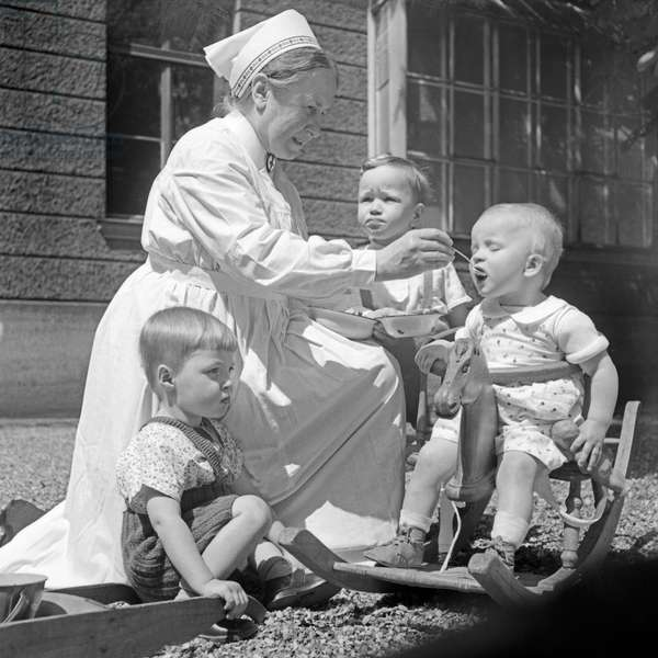 A sister feeding toddlers in the courtyard of the Red Cross hospital children medical unit at Munich, Germany 1930s (b/w photo)