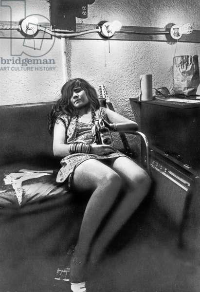 American singer Janis Joplin with a bottle of Souther Comfort after a concert, USA 1960s