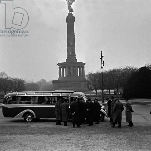 A traveller group ion front of their coach at the Berlin Victory column, Germany 1930s (b/w photo)