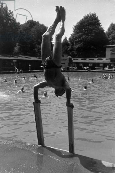 A bather pulling off acrobatic feats in an open air bath in Stuttgart, Germany 1930s (b/w photo)
