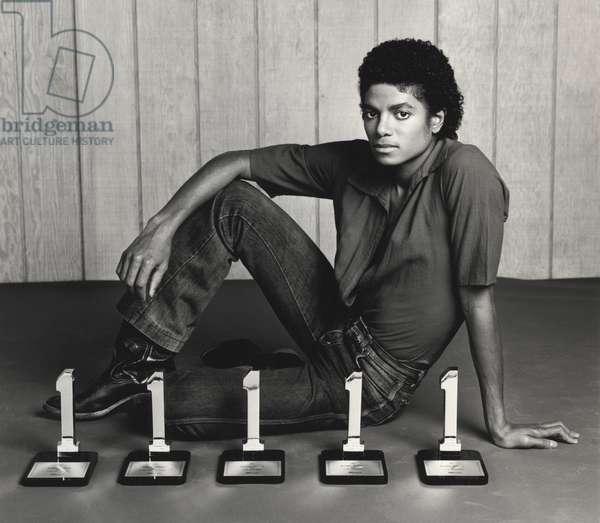 Le chanteur americain Michael Jackson vers 1985 posant avec ses recompenses Billboard award.