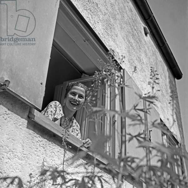 A young woman looking out of the window to her garden, Germany 1930s (b/w photo)