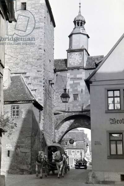A horse-drawn carriage is driving through one of the many gate archways in Rothenburg ob der Tauber, Germany 1930s (b/w photo)