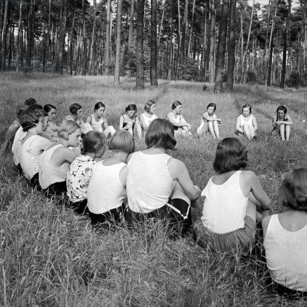 Girls are sitting in a circle in the forest at Altenhof, Brandenburg, 1930s (b/w photo)