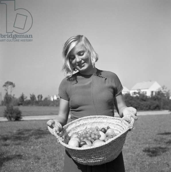 A young woman in the garden in summertime, Germany 1930s (b/w photo)