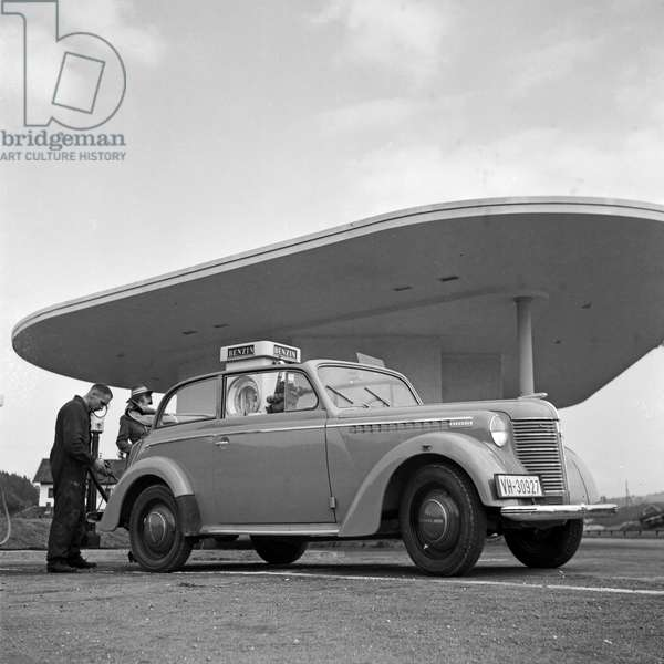 At the petrol station with an Opel Olympia, Germany 1930s (b/w photo)