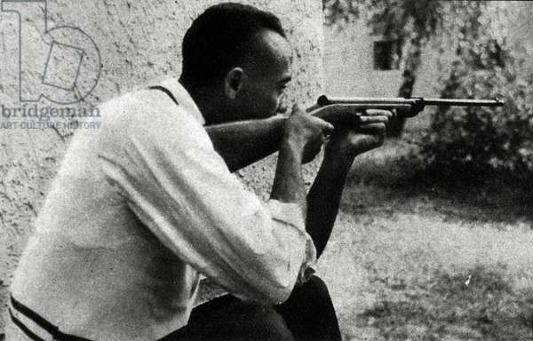 1936 Olympic Games. Berlin. USA's JESSE OWENS (four Gold Medals) shooting with a gun.
