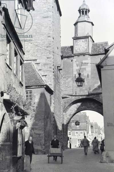 A hustle and bustle on a street with one of the many towers and archways in Rothenburg ob der Tauber, Germany 1930s (b/w photo)