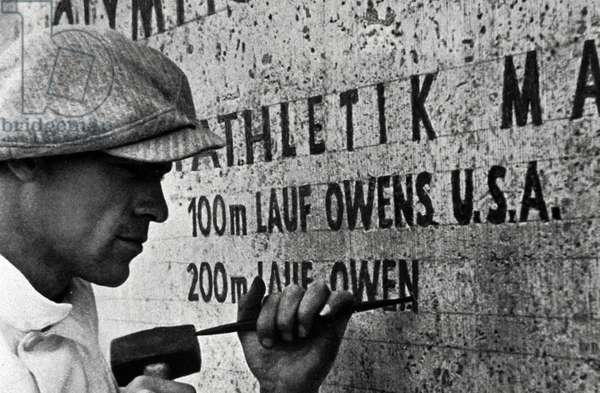 1936 Olympic Games. Berlin. A stonemason at work records the feat of Jesse Owens, USA, winner of 4 Gold Medals.