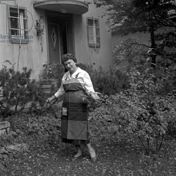 A housewife posing at the autumnal front garden of her house at Hamburg, Germany 1950s