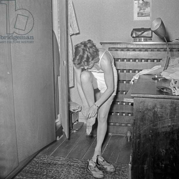 Young girl steps in a hurry into her stockings, Germany 1950s