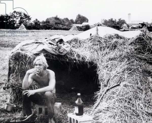 """Jeune spectateur assis devant la tente, fumant une cigarette. Scene tiree du Film documentaire """"""""Woodstock"""""""" de Michael Wadleigh tourne lors du festival de musique, emblematique du mouvement hippie, qui eut lieu entre le 15 et le 18 aout 1969."""