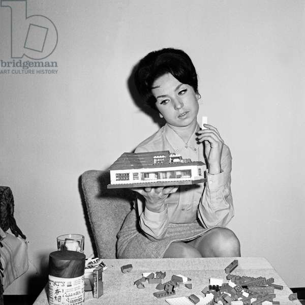 German TV speaker and presenter Brigitte Gerloff constructing a house with lego toy bricks, Germany 1960s