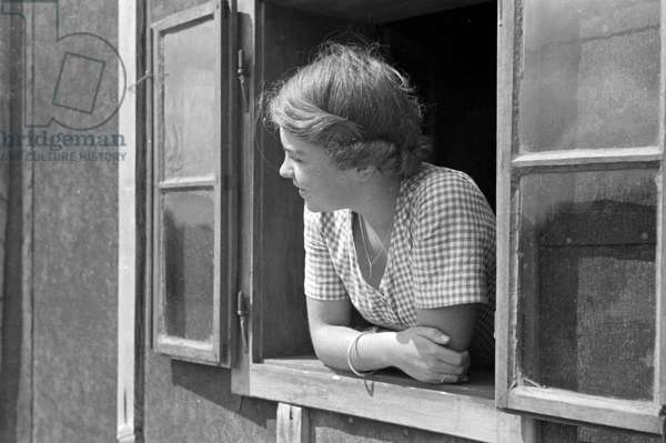 A young woman looking out of the window, Germany 1930s (b/w photo)