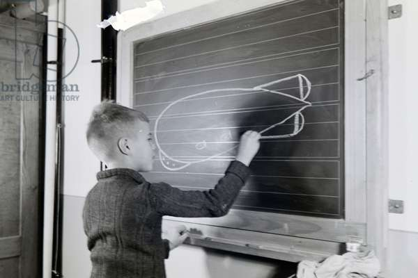"A little school boy is drawing the German airship ""Graf Zeppelin"" with chalk on a blackboard, zeppelin village near Frankfurt am Main, Germany 1930s (b/w photo)"