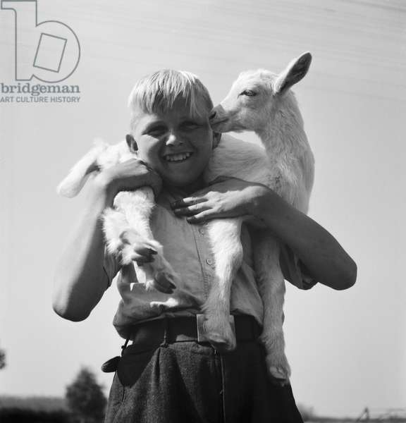 Children playing with a little lamb, Germany 1930s (b/w photo)