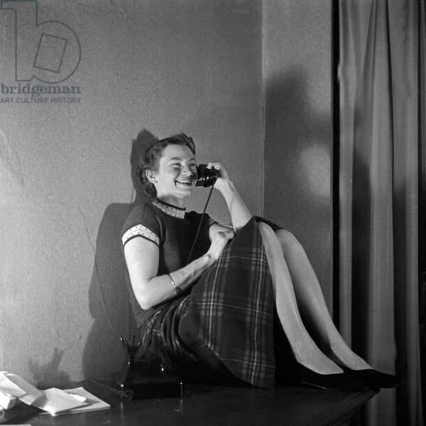 A young girl sitting ion a sideboard and having a phone call, Germany 1950s