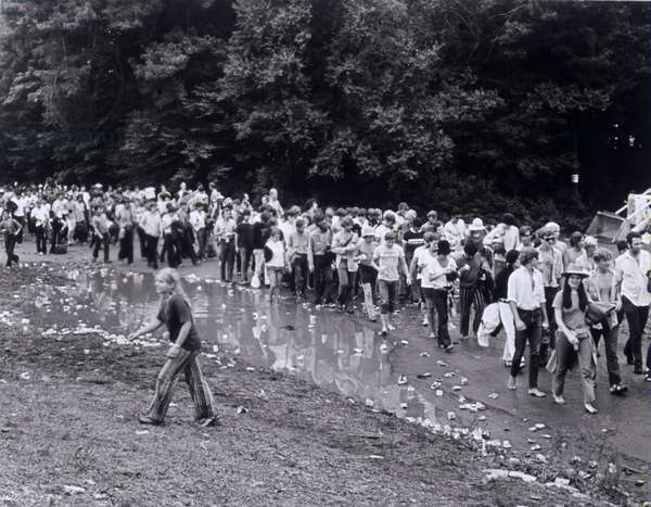 """Le public marchant dans la boue. Scene tiree du Film documentaire """"""""Woodstock"""""""" de Michael Wadleigh tourne lors du festival de musique, emblematique du mouvement hippie, qui eut lieu entre le 15 et le 18 aout 1969."""