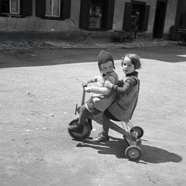 Two children playing with a three wheeler, Germany 1930s (b/w photo)