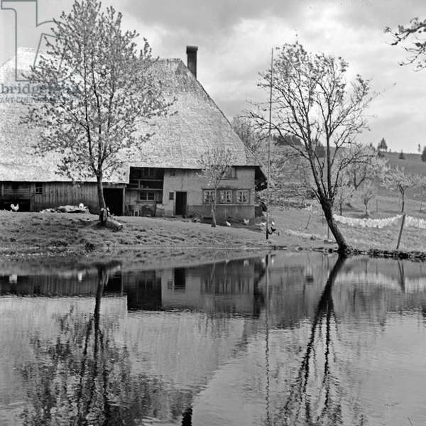 A Black Forest farm house reflecting in the water of a pond, Germany 1930s (b/w photo)
