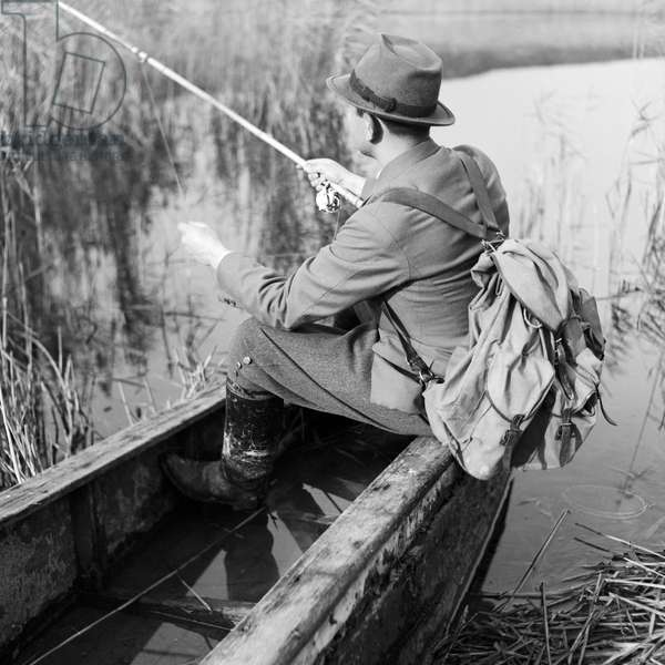 A man sitting in a rowing boat is fishing, Germany 1930s (b/w photo)