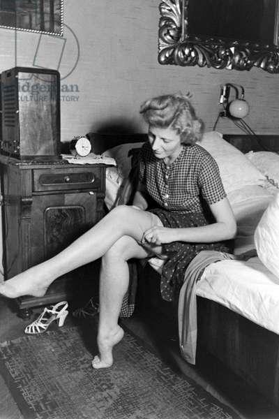 Woman putting on her stockings, Vienna, 1930s (b/w photo)