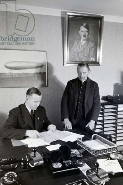 The first mayor of the zeppelin village, Hans von Schiller, and an employee in his bureau with a portrait of Adolf Hitler hanging above the desk, Germany 1930s