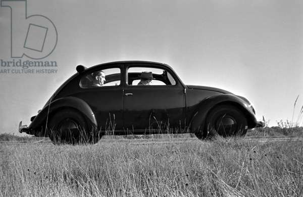 The Volkswagen beetle, or KdF car, with open roof on the test track near Wolfsburg, Germany 1930s (b/w photo)