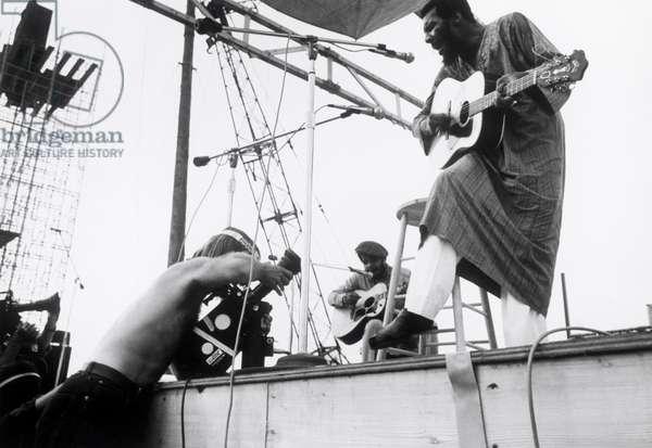 """Le musicien de folk Richie Havens. Scene tiree du Film documentaire """"""""Woodstock"""""""" de Michael Wadleigh tourne lors du festival de musique, emblematique du mouvement hippie, qui eut lieu entre le 15 et le 18 aout 1969."""