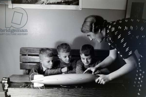 A teacher is explaining a zeppelin model to three school boys who are listening with great interest, zeppelin village near Frankfurt am Main, Germany 1930s (b/w photo)