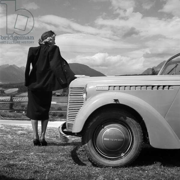 A young woman standing by the bonnet of an Opel model Olympia, Austria 1930s (b/w photo)