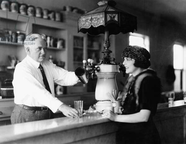 Man Serving Beverage to Woman at Counter