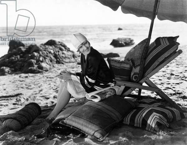 Woman Relaxing Under Umbrella on Beach