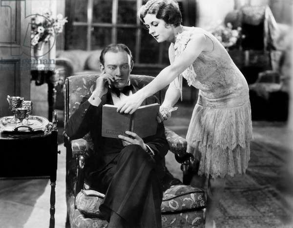 Profile of a Young Woman Showing a Book to a Man Sitting in an Armchair