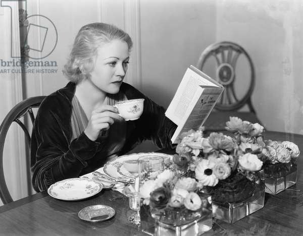 Young Woman Sitting at the Dining Table Holding a Cup of Tea and Reading a Book