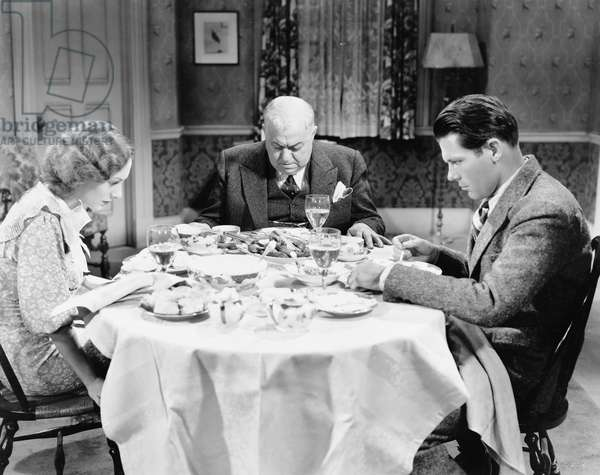 Couple with Their Father Sitting at the Dining Table and Praying
