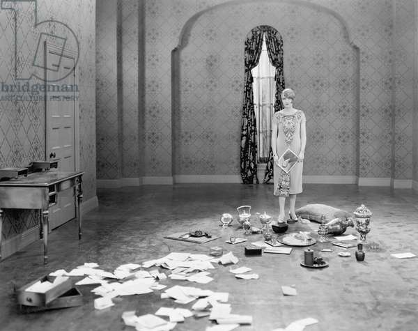 Woman Standing in an Empty Room Scattered with Letters