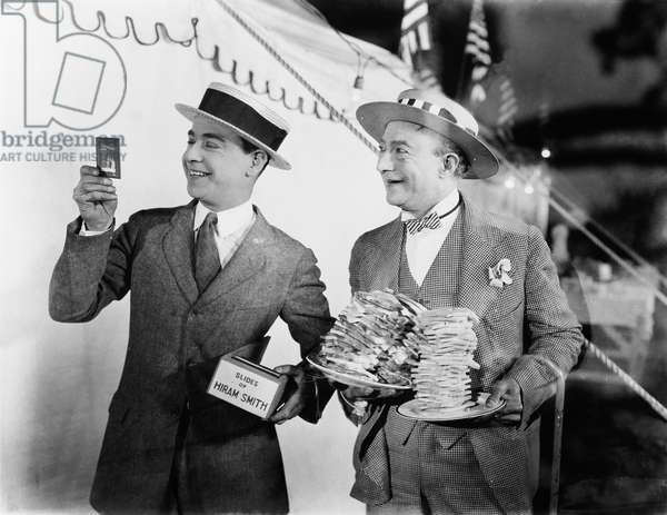 Man Holding Plates of Sandwiches with a Man Looking at a Film Slide Beside Him