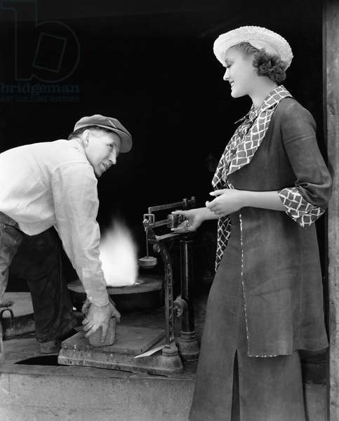 Woman with Man at Foundry Weighing Silver