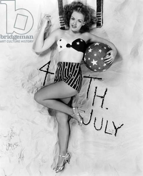 Beautiful woman with 4th July written in the sand, 1910-40 (b/w photo)